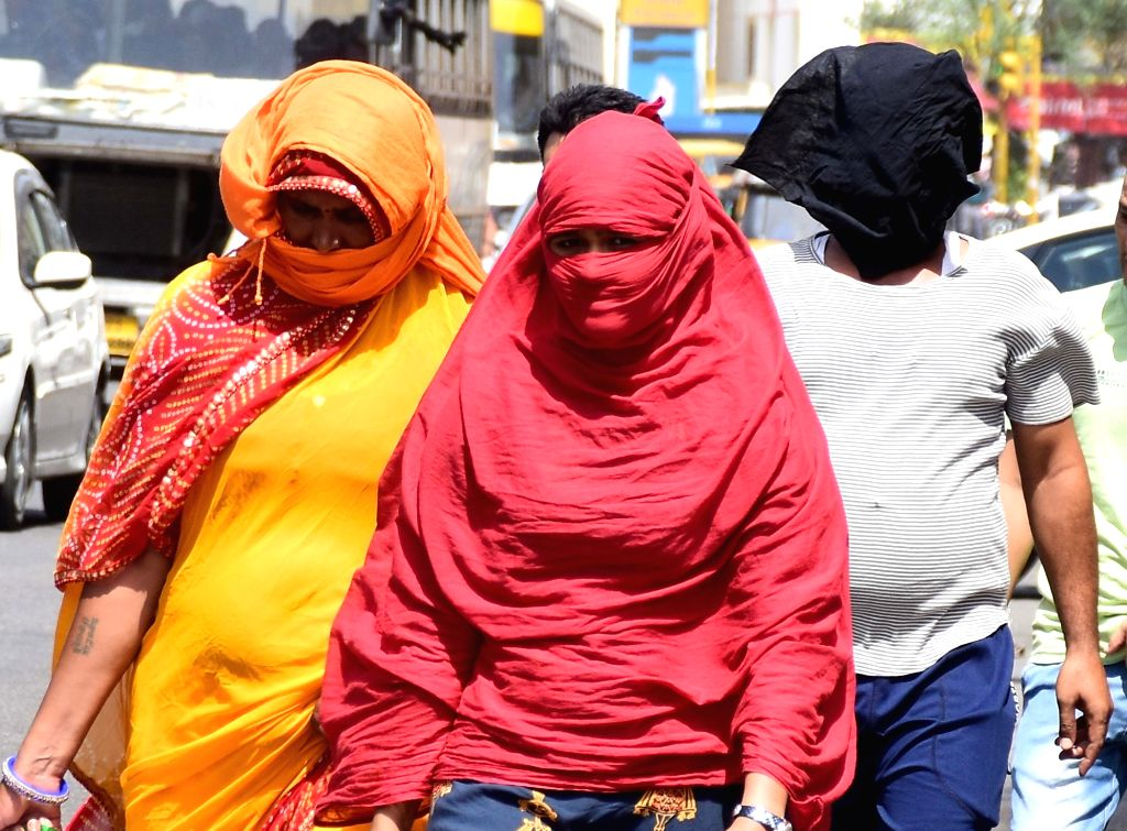 People use scarfs to shield themselves from the scorching sun on a hot day, in Jaipur, on June 2, 2019.
