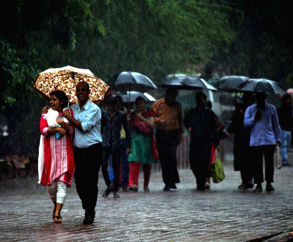 People use umbrella to protect themselves from rains in Agra, on July 27, 2016.