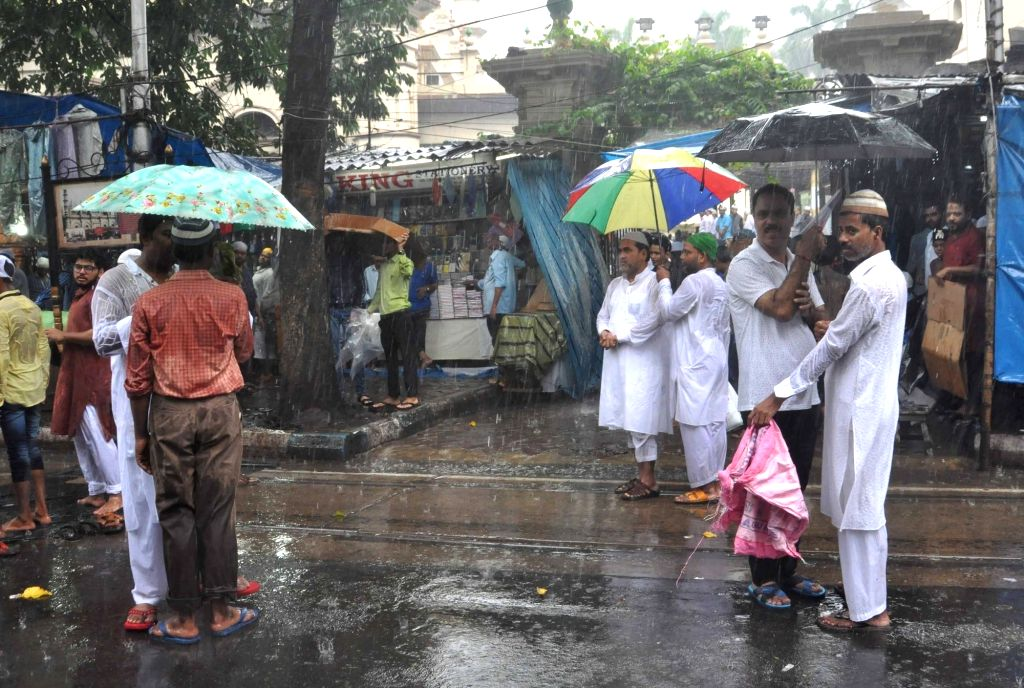 People use umbrellas to protect themselves from rains in Kolkata on June 23, 2017.