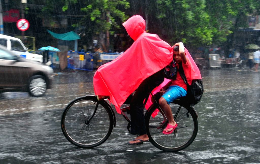 People use umbrellas to protect themselves from rains in Kolkata on June 24, 2017.