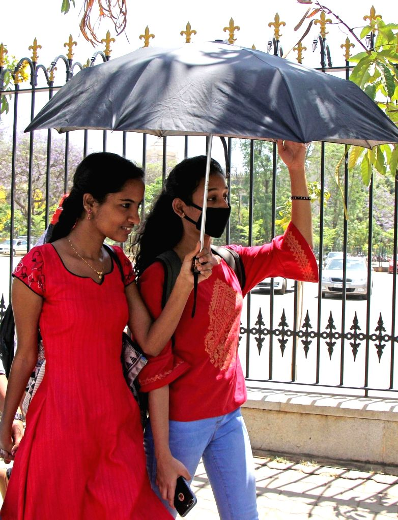 People use umbrellas to protect themselves from scorching sun in Bengaluru on March 7, 2019.