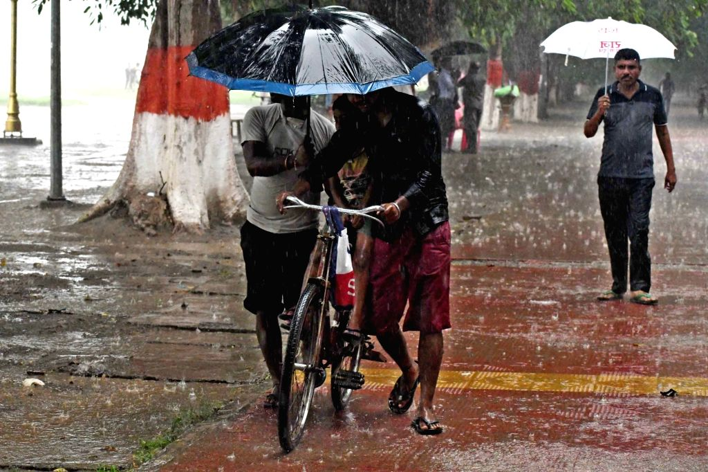 People use umbrellas to shield themselves during rains in Patna on Sep 13, 2019.