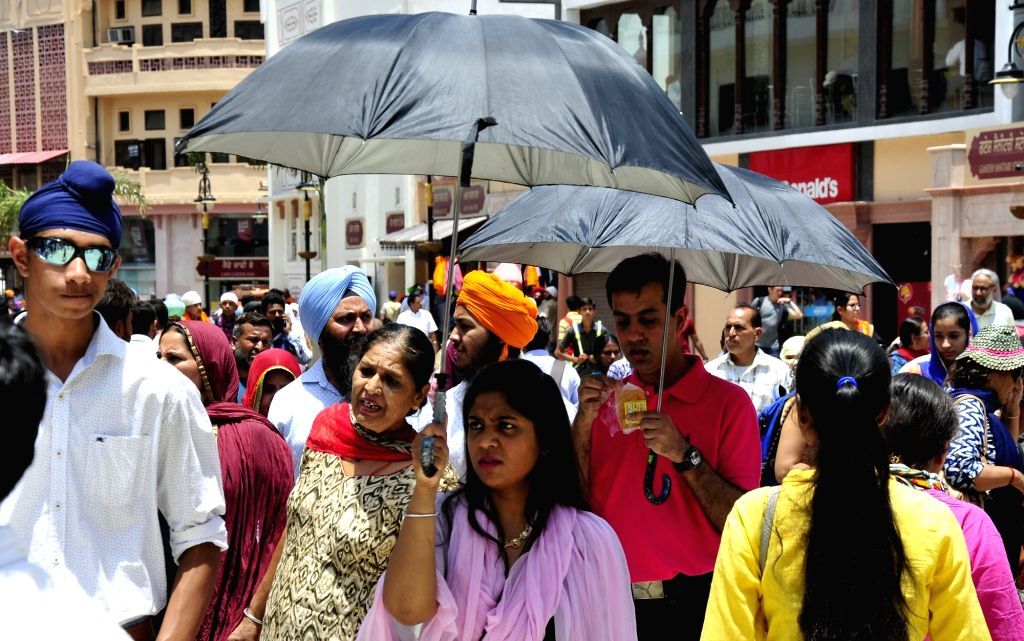 People use umbrellas to shield themselves from scorching sun in Amritsar on June 13, 2017.