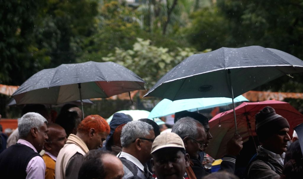 People use umbrellas to shield themselves from rains that lashed Delhi on Feb 20, 2019.