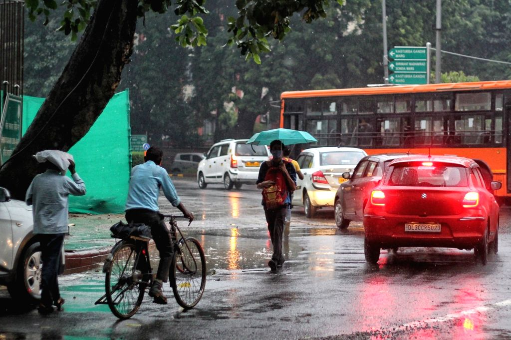 People uses an Umbrella during rain in New Delhi on Tuesday October 02, 2021