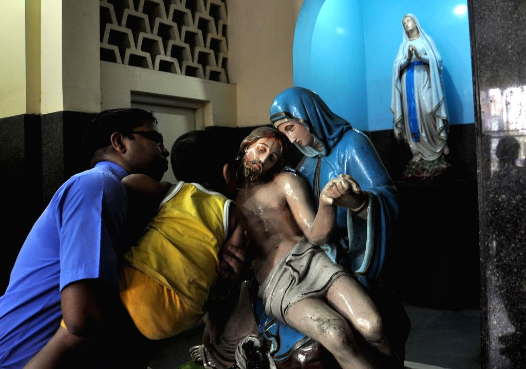 People visit church on Good Friday in Kolkata on April 18, 2014.
