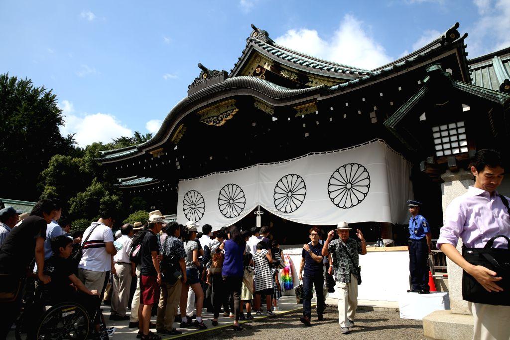 People visit the Yasukuni Shrine in Tokyo, Japan, Aug. 15, 2015. Japanese Prime Minister Shinzo Abe on Saturday sent a ritual offering to the war-linked Yasukuni ... - Shinzo Abe