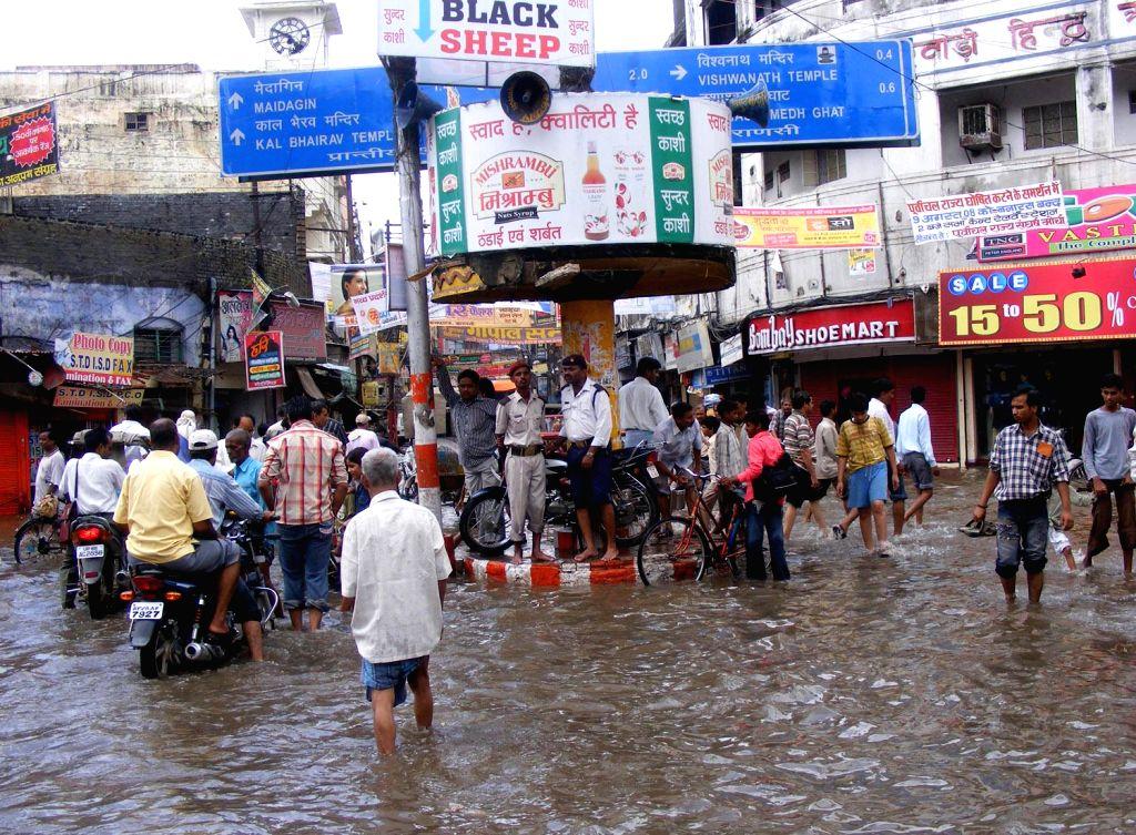 People wade though waterlogged streets of Varanasi on June 27, 2014.