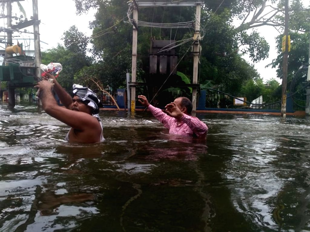 People wade through a flooded street in Patna's Rajendra Nagar, on Sep 30, 2019.