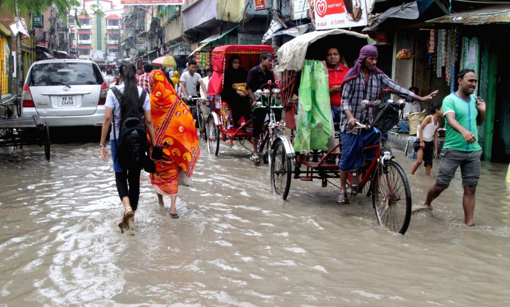 People wade through a water-logged streets of Kolkata on March 9, 2017.