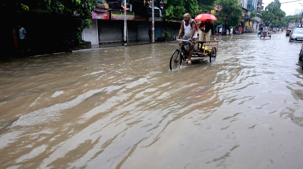 People wade through a waterlogged road during heavy rain in Kolkata on Thursday 17 June 2021.