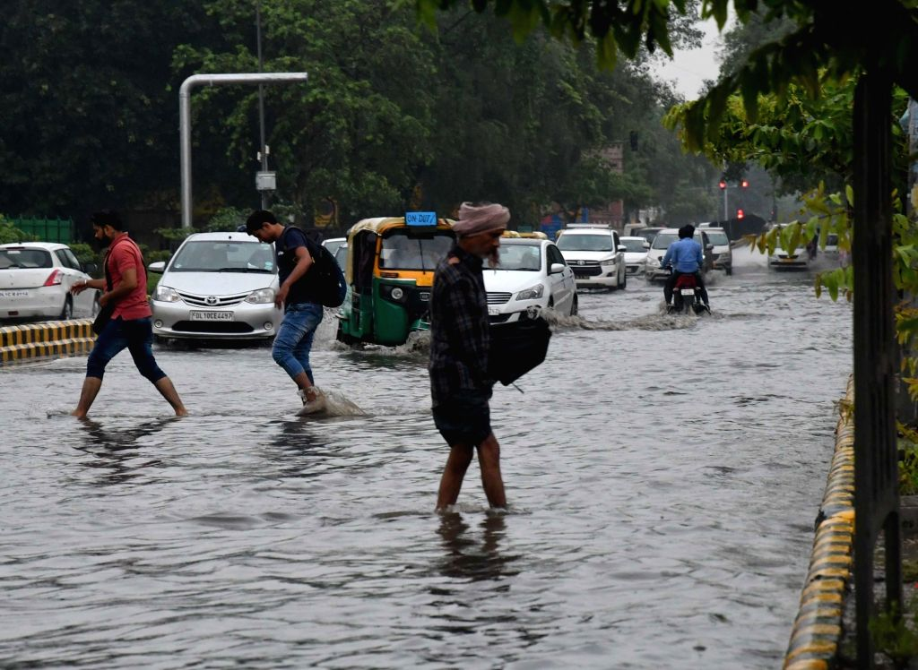 People wade through a waterlogged street in New Delhi, after heavy rains lashed the national capital on July 13, 2018.