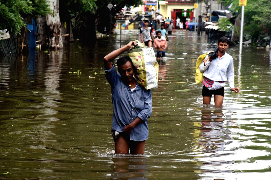 People wade through an inundated street of the flood affected Patna, on Sep 30, 2019.