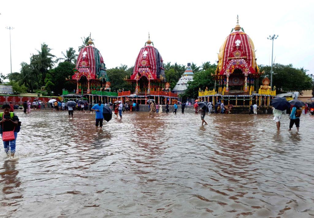 People wade through flood water in Puri, Odisha on July 21, 2018.
