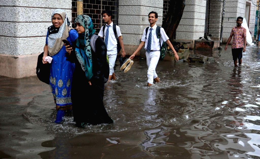 People wade through flooded streets of Kolkata on Aug 3, 2017.