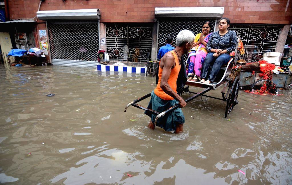 People wade through flooded streets of Kolkata, on 29 Sep, 2019.