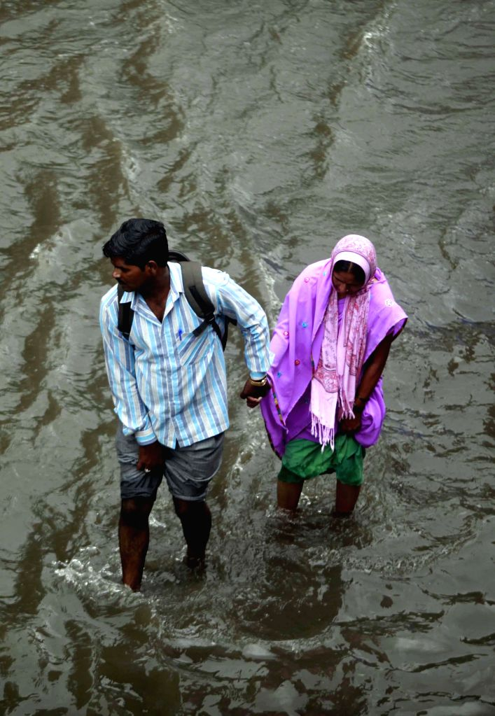 People wade through flooded streets of  Mumbai after heavy rains in Mumbai on July 16, 2014.
