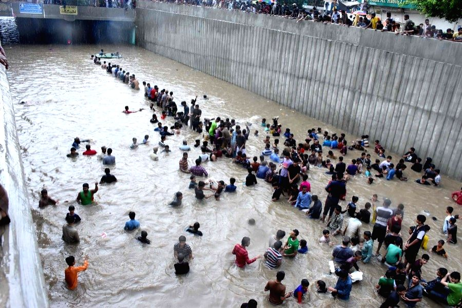 People wade through floodwater after a heavy rain in southern Pakistani port city of Karachi on Aug. 27, 2020.