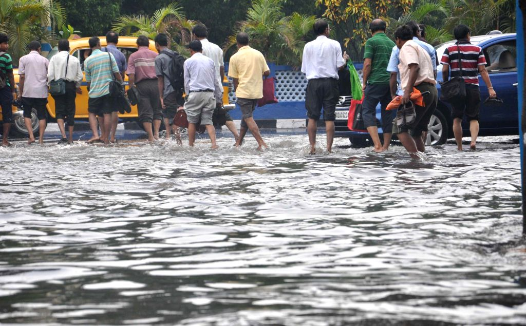 People wade through water logged roads after heavy rains in Kolkata on June 17, 2014.