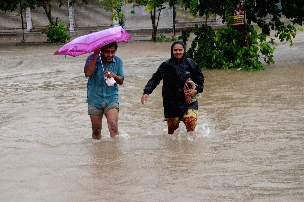 People wade through water-logged streets of Ahmedabad, on July 29, 2015.