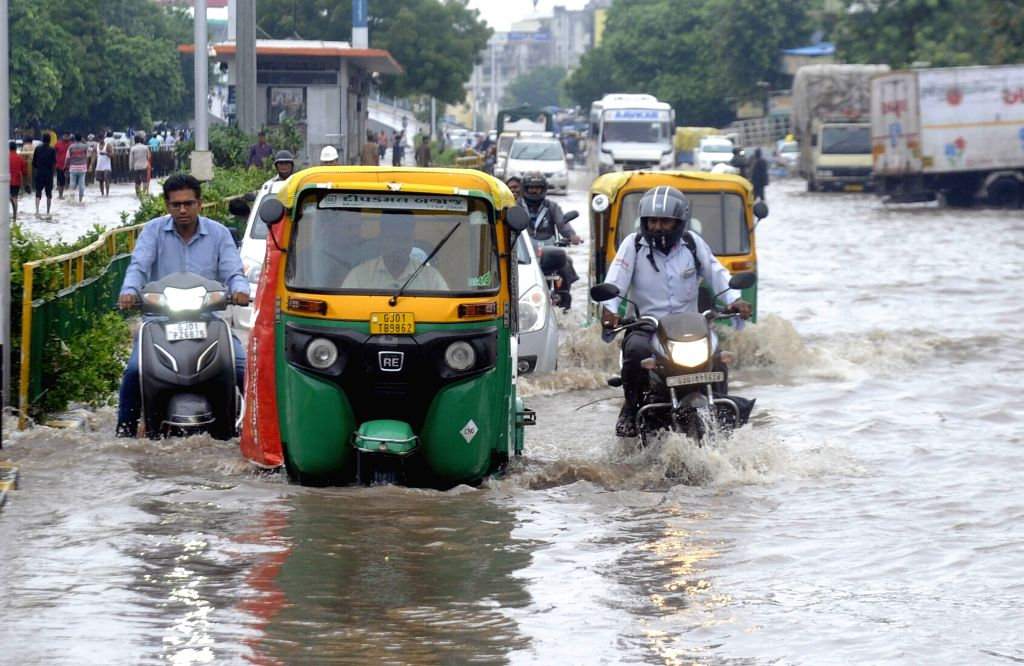 People wade through water logged streets of Ahmedabad on Aug 10, 2019.
