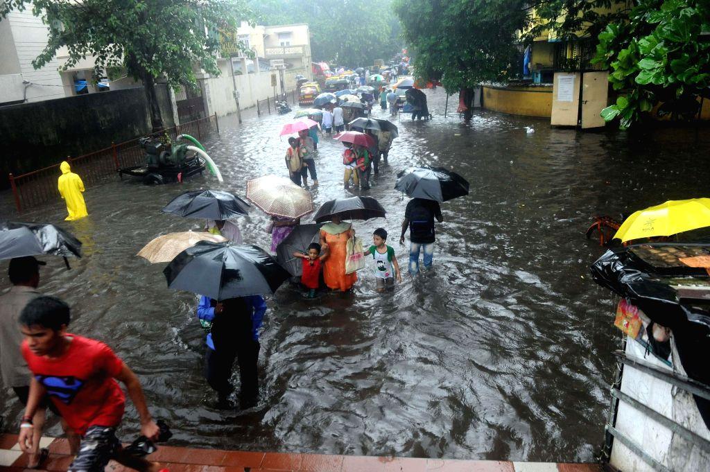 People wade through waterlogged roads of Mumbai during rains on July 31, 2014.
