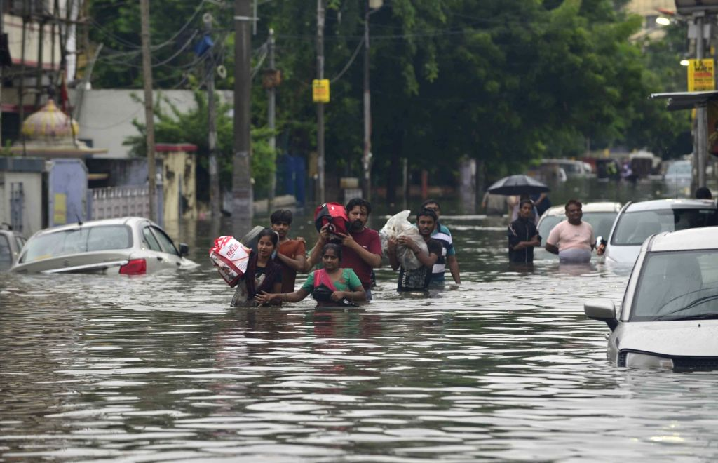 People wade through waterlogged streets, as the locality remains flooded in Patna, on 29 Sep, 2019.