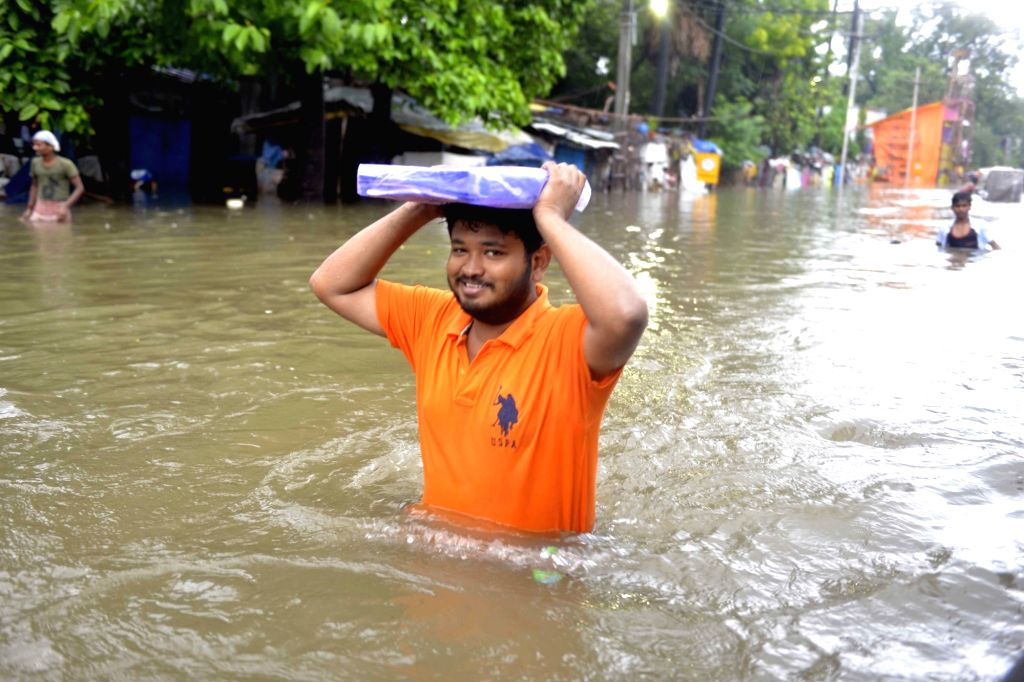 People wade through waterlogged streets to buy essentials, as the locality remains flooded in Patna, on 29 Sep, 2019.