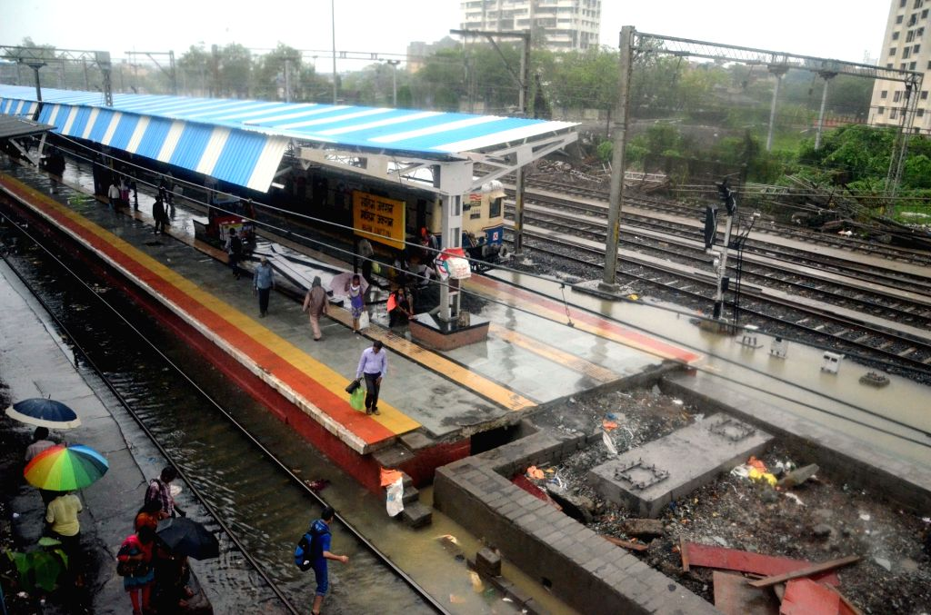 People wait for a trian on a submerged track as heavy rain hit train services in Mumbai on July 2, 2016.