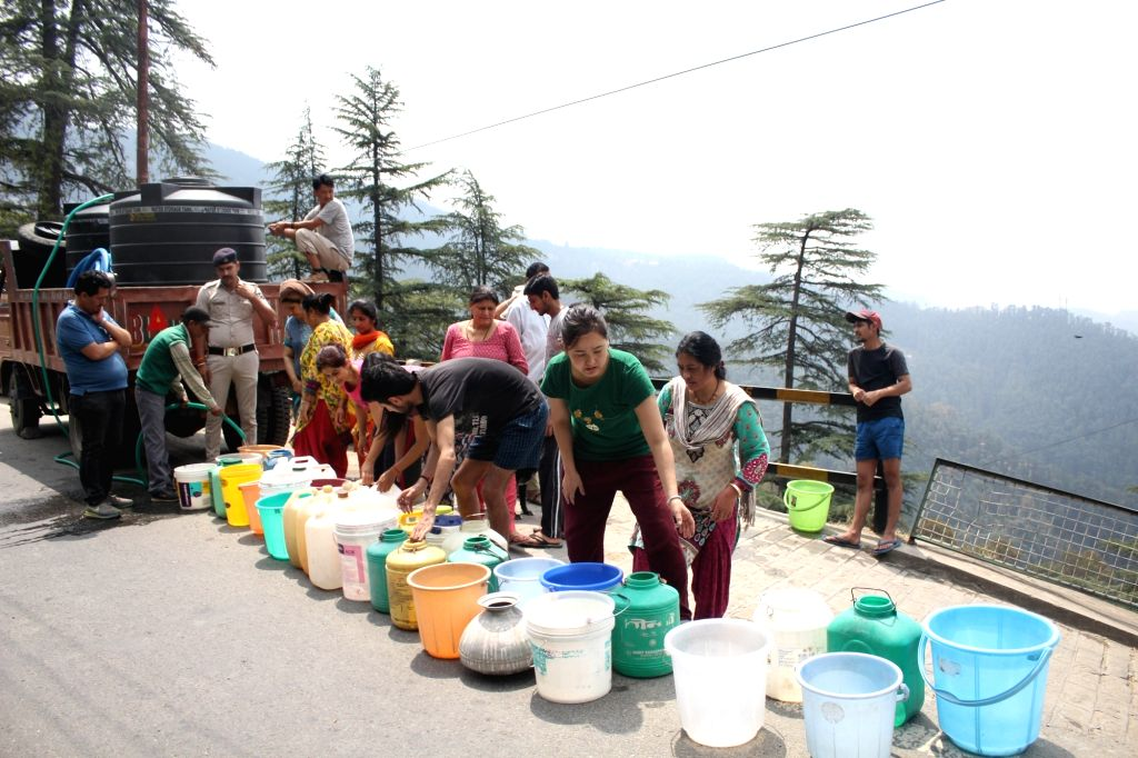 People wait for their turn to collect potable water as water crisis hits Shimla on June 1, 2018.