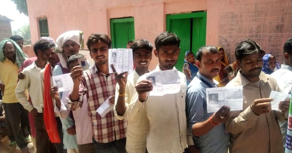 People wait in a queue to cast their votes for the 2019 Lok Sabha elections in Bihar's Aurangabad, on April 11, 2019.