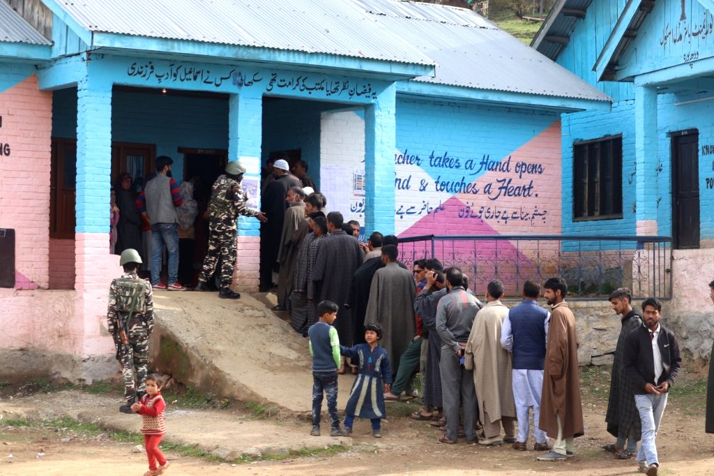 People wait in a queue to cast their votes for the first phase of 2019 Lok Sabha elections, at a polling booth in Jammu and Kashmir's Kupwara district, on April 11, 2019.