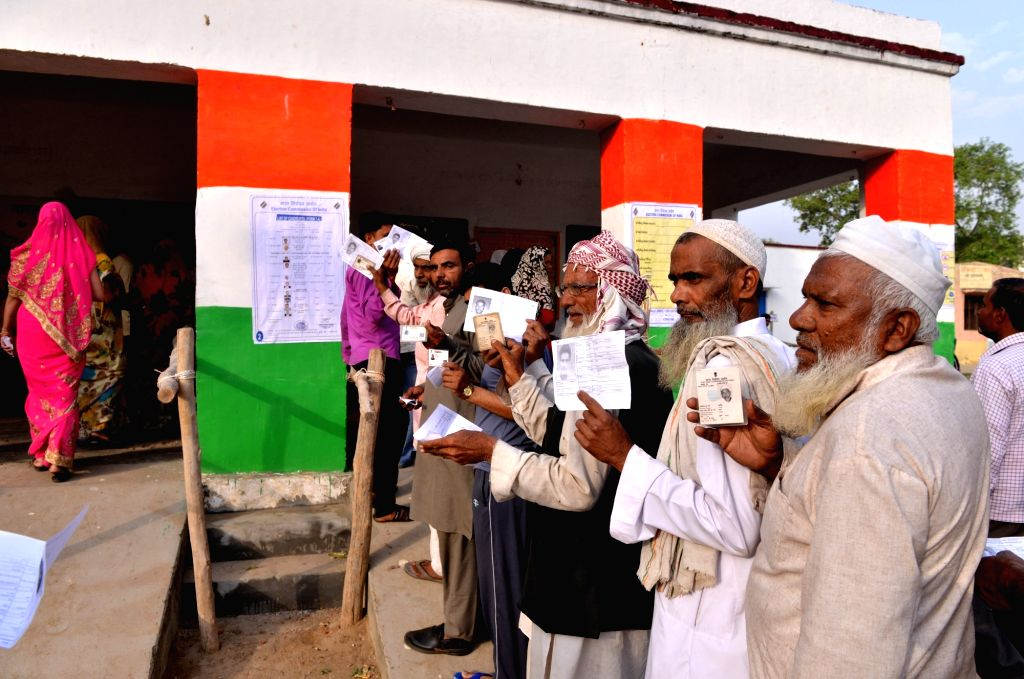 People wait outside a polling booth to caste their vote for the 2019 Lok Sabha elections in Navala village Uttar PradeshMuzaffarnagar district, on April 11, 2019.