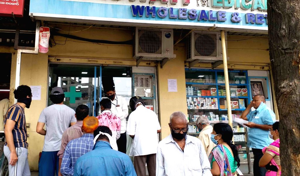 People wait outside a wholesale medicine shop during the fifth phase of the nationwide lockdown imposed to mitigate the spread of coronavirus, at Begum bazzer in Hyderabad on June 26, 2020.