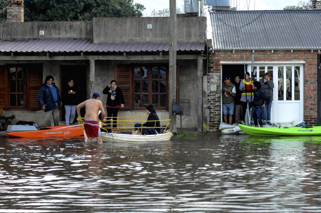People wait to be moved at a flooded road in Salto city, Buenos Aires province, Argentina, on Aug. 11, 2015. According to local press, the heavy rains in the province ...