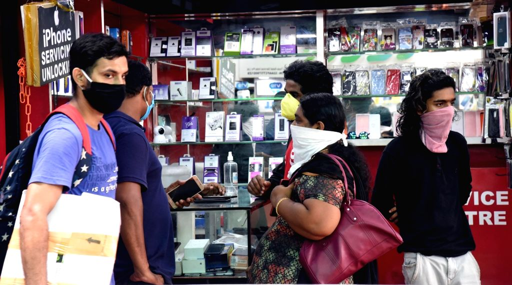 People waiting in front of a mobile phone shop for purchasing and repairing during the nationwide lockdown, in wake of coronavirus pandemic in Kochi on April 26, 2020.