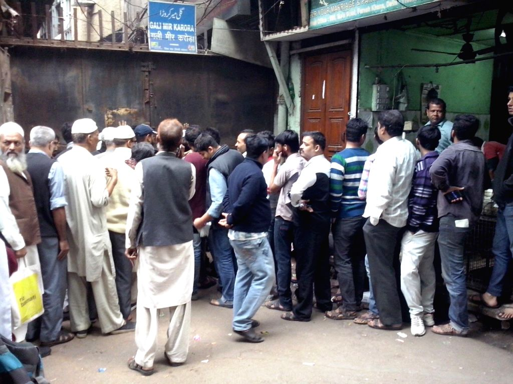 People waiting outside a Central Bank of India branch at Lal Kuan in Old Delhi on Wednesday.