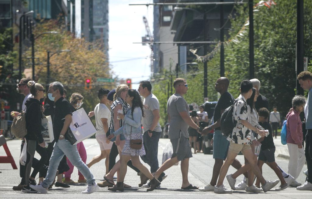 People walk across a street in Vancouver, British Columbia, Canada, on July 12, 2020. In the past week, the number of new cases in British Columbia has increased ...