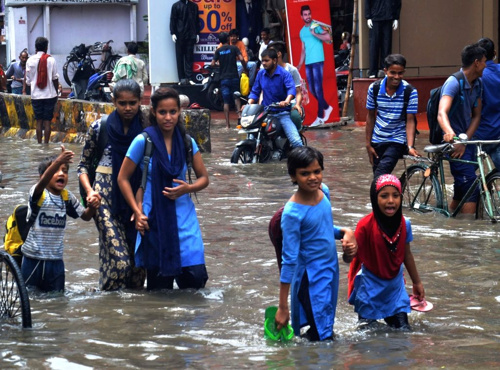 People walk across a water-logged street after rains, in Patna on July 25, 2019.