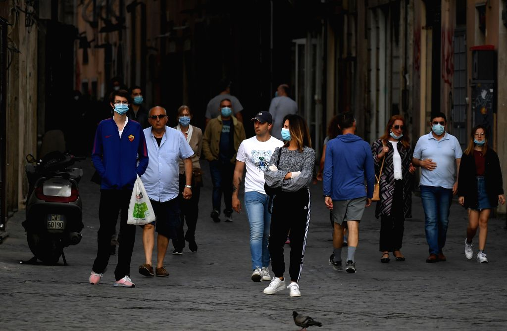 People walk along a street in Rome, Italy, on May 8, 2020. Italy on Friday posted a decrease in COVID-19 intensive care cases and hospitalizations as the death toll ...