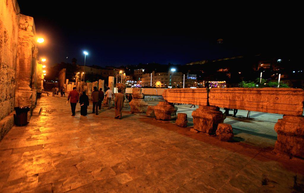 People walk at the Roman Amphitheater in Amman, Jordan, on Aug. 17, 2015.