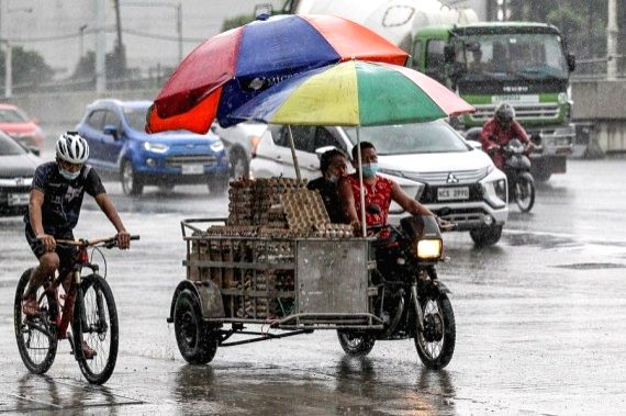 People walk in the rain brought by typhoon Molave in Manila, the Philippines on Oct. 25, 2020.