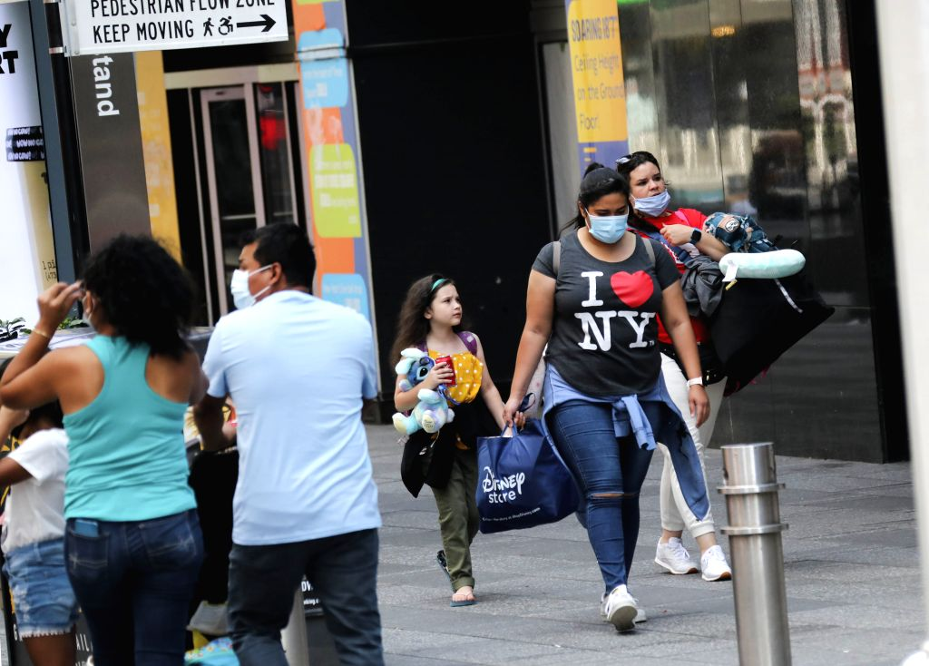People walk in Times Square in New York, the United States, on Aug. 9, 2020. The total number of COVID-19 cases in the United States surpassed the 5 million mark on ...