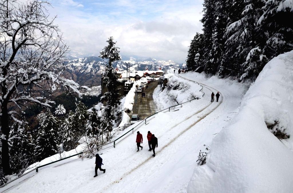 People walk on a snow-covered road in Himachal Pradesh's Kufri, on Feb 19, 2019.