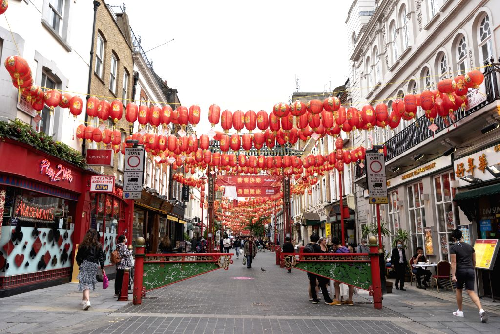 People walk on a street at Chinatown in London, Britain, on July 4, 2020. Millions of people in England emerged from the COVID-19 lockdown on the so called ...