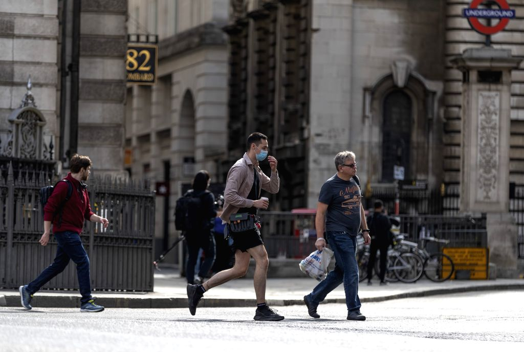 People walk on a street in central London, Britain, on Sept. 12, 2020. Almost 8 million Britons will be subjected to tighter lockdown restrictions next week after ...