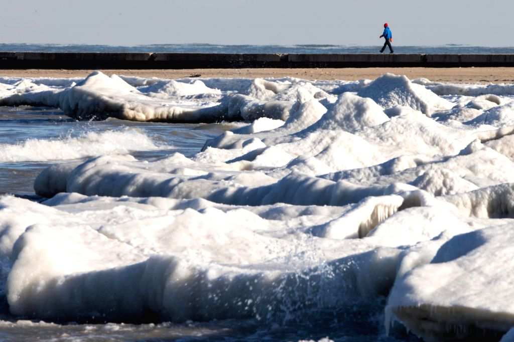 People walk on frozen beaches along Lake Michigan as negative degree wind chill weather continues in Chicago, Illinois, United States of America on Jan, 18, 2016. ...