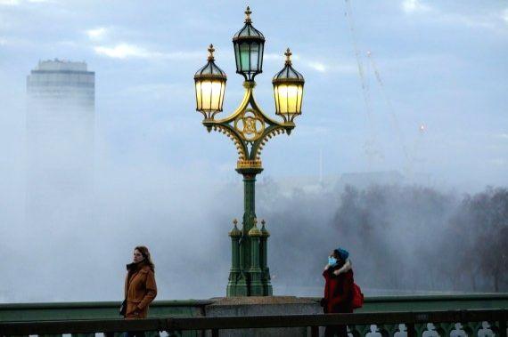 People walk on Westminster Bridge, in London, Britain, Nov. 27, 2020.