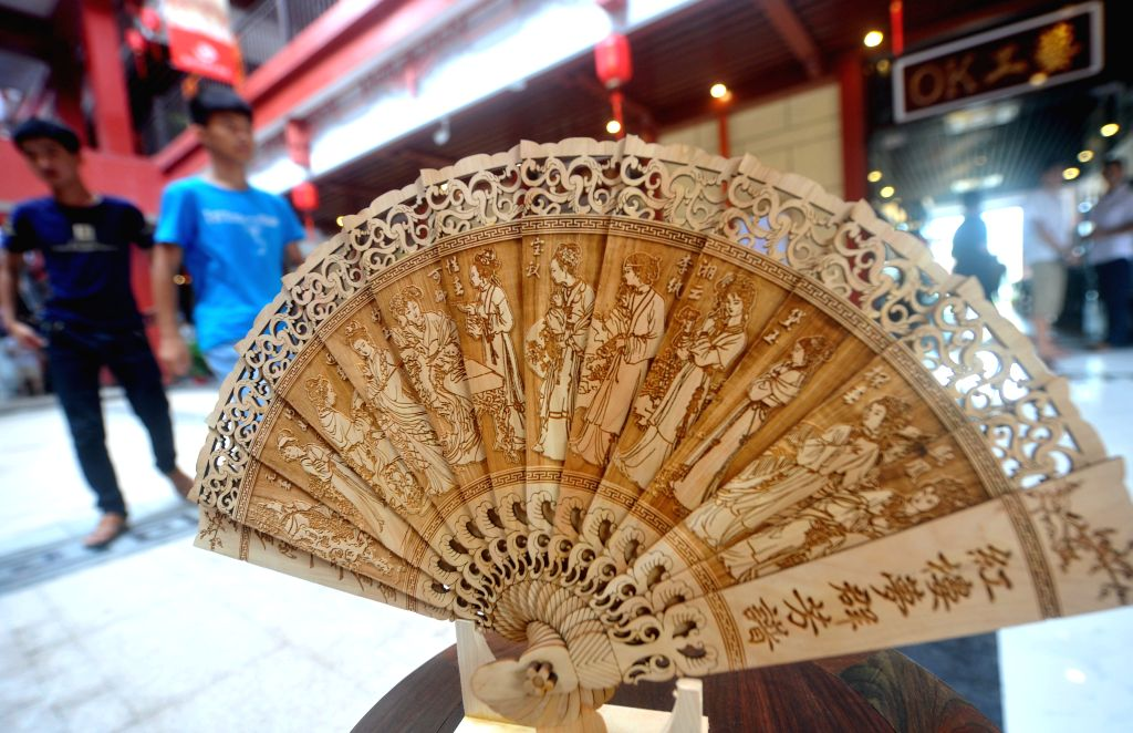 People walk past a wooden fan displayed during a wood art show in Xianyou, southeast China's Fujian Province, June 25, 2015. A wood art show was held in Duwei ...