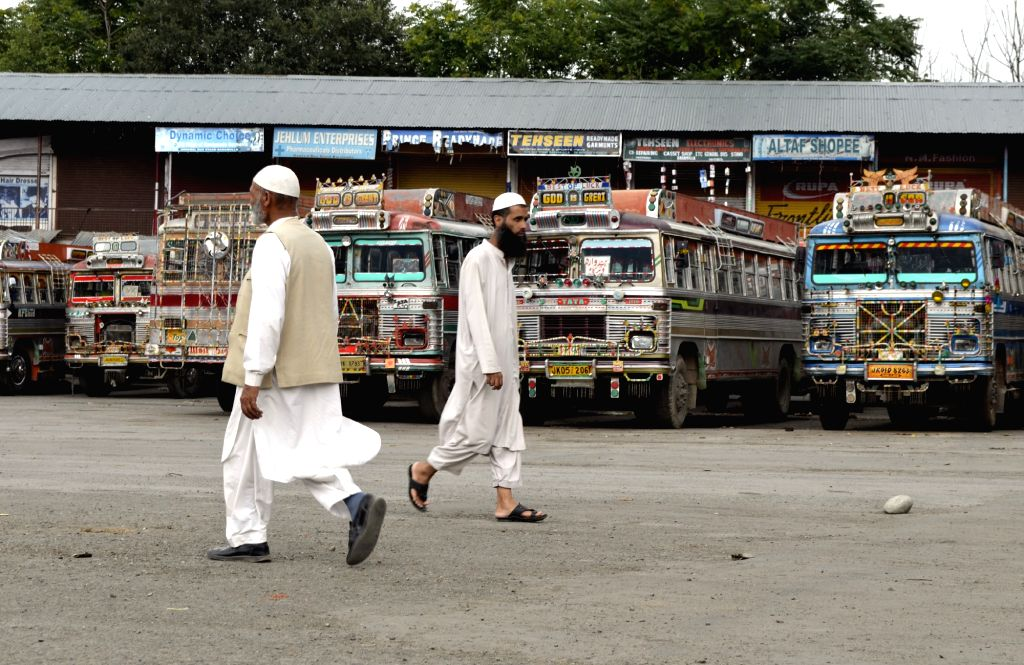 People walk past at a deserted J&K State Road Transport Corporation Depot in Baramulla as curfew continued for the 6th day in most parts of the Kashmir valley where 37 people died in ...
